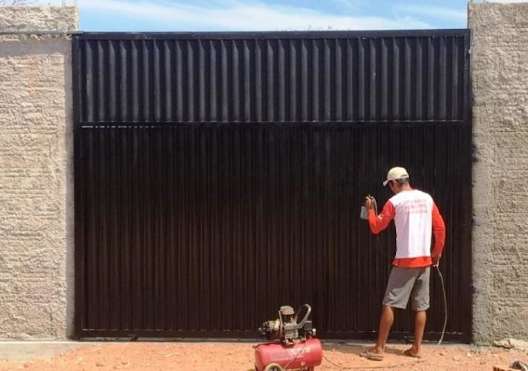 Preso pintando portão