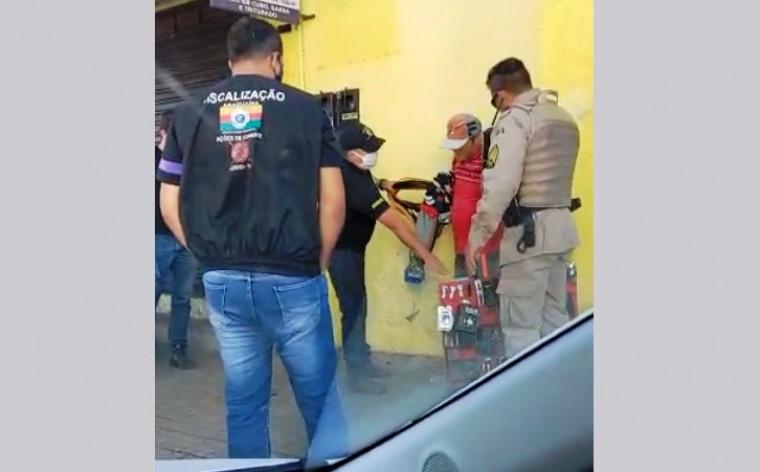 Vendedor ambulante cercado por fiscais e PM