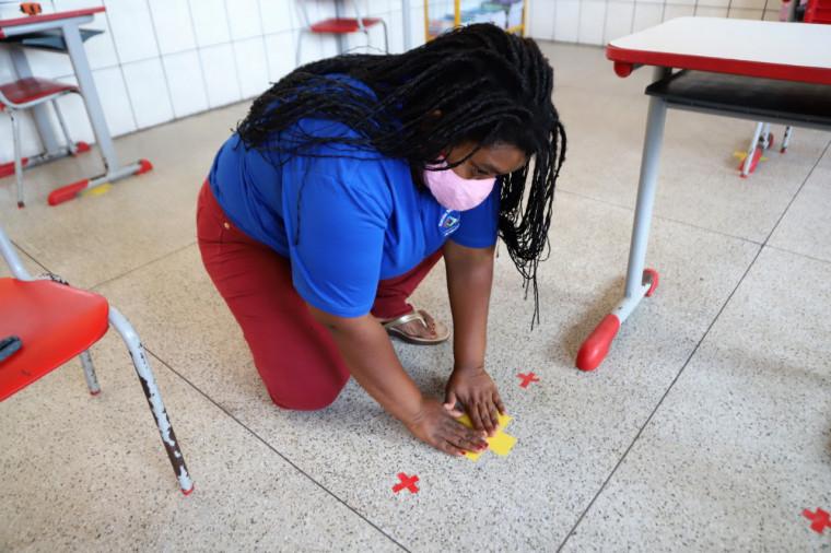 Fitas amarelas foram colocadas nos corredores e na entrada da escola marcando o distanciamento adequado entre as crianças
