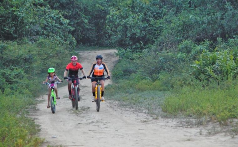 Menina pedalando com o casal