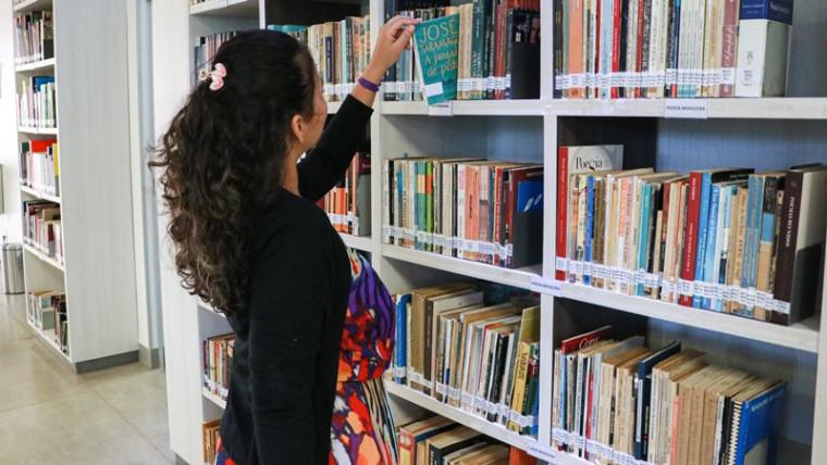 Mulher pega livro em biblioteca