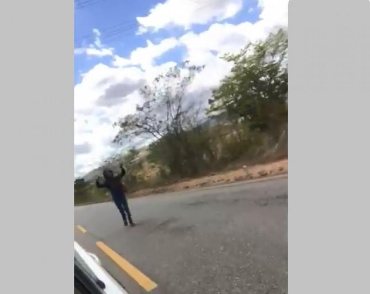 Mulher andando de preto às margens da BR-153