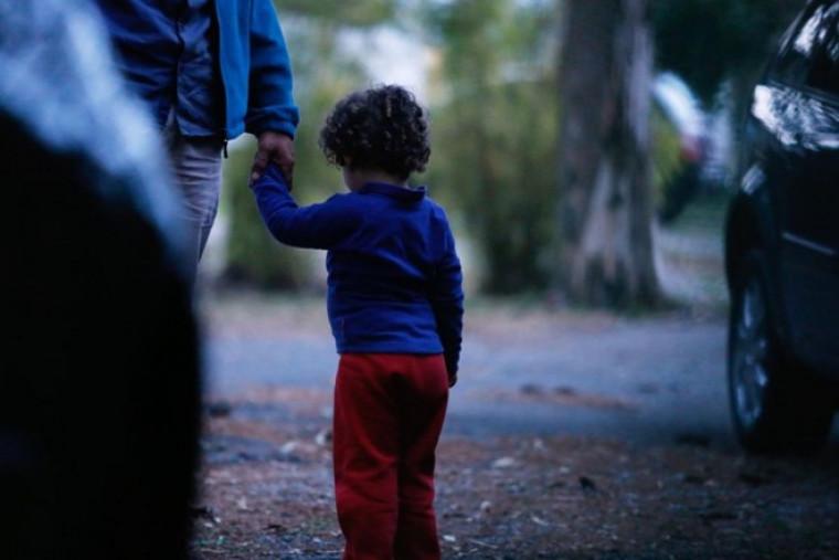 Criança segura mão de uma pessoa adulta